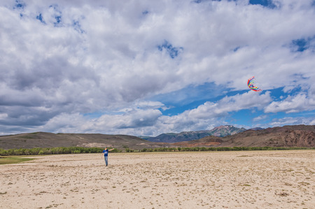 The desert mountain landscape with a young man who runs the multicolored kite. photo