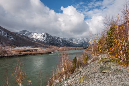 Autumn landscape with the river, the mountains in the snow, trees and clouds photo