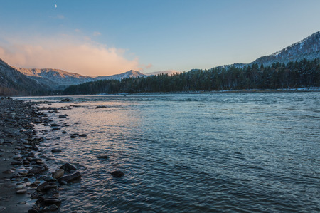 Evening landscape with river, mountains and trees on the shore. photo