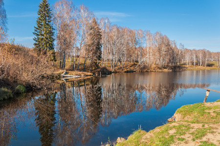 Beautiful landscape with the quiet calm river, a reflection of the birchs and spruce, sky and clouds. photo