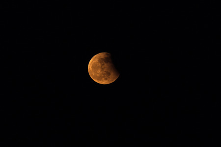 lunar eclipse: View of the moon on a black background during a partial lunar eclipse