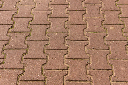 trapezoid: Abstract geometric background of brown paving slabs in a trapezoid shape, laid out on the pavement
