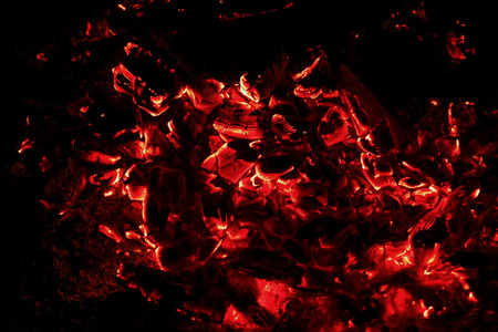 smoldering: Black and red abstract background of smoldering and burning coals in the fire on a black background