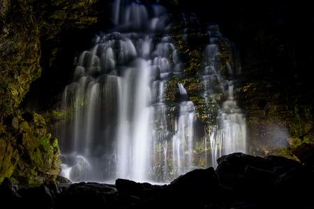 Bella vista di notte della cascata con retroilluminazione tra le rocce e le pietre, girato lunga esposizione