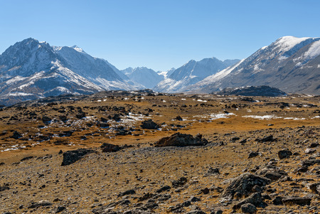sparse: Scenic autumn mountain landscape with mountains covered with stones and sparse vegetation on the background of snowy mountains and blue sky Stock Photo