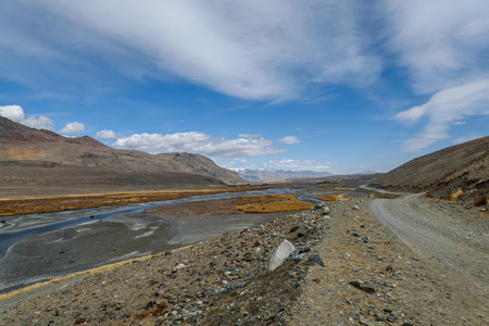 macadam: The picturesque steppe landscape with mountains, winding river, rocky road along the river and the autumn vegetation on a background of blue sky and beautiful fluffy clouds