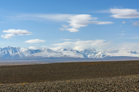 lenticular: The picturesque steppe autumn landscape with snow covered mountains, steppes with sparse vegetation on a background of blue sky with beautiful fluffy and lenticular clouds