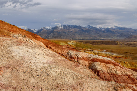 sparse: The picturesque steppe desert landscape with multicolored mountains, cracks in the ground and sparse vegetation on the background of other mountains and cloudy sky in autumn