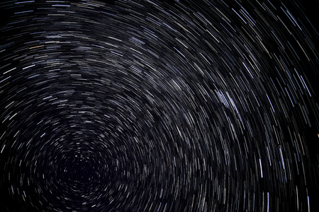 north star: Abstract decorative background with swirls traces of stars revolving around the North Star on the background of the black night sky, shot long exposure