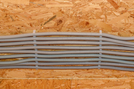 plastic conduit: Gray plastic corrugated pipes with electric cables, reinforced ceiling newly constructed wooden house