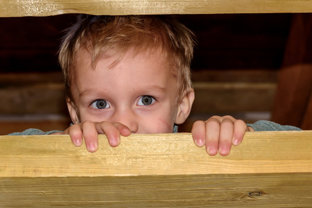 smeared hand: Portrait of a little boy playing hide and seek, amid the wooden stairs in the barn Stock Photo