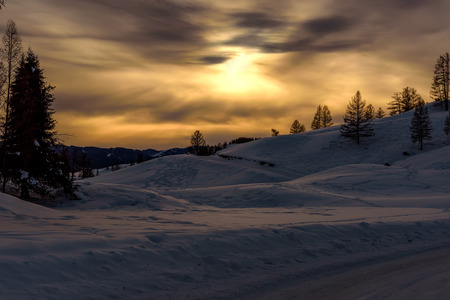 snow tree: Scenic winter view with mountains covered with snow, trees and snowdrifts on the background of the setting sun and the sky with clouds Stock Photo