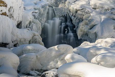 water frozen: Scenic view on a waterfall with beautiful patterns of frozen water, with water, icicles and snowdrifts in the winter