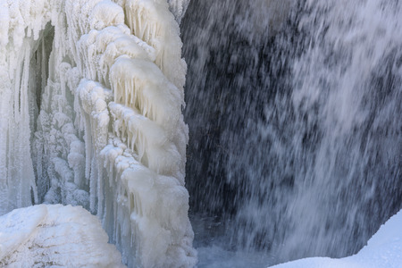 snowdrifts: Scenic view on a waterfall with beautiful patterns of frozen water, with water, icicles and snowdrifts in the winter