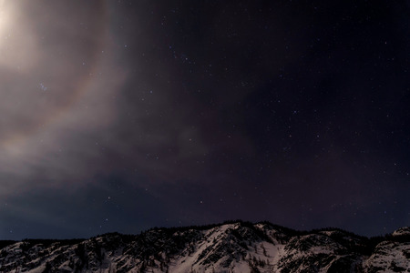 winter sky: Beautiful winter night landscape with mountains covered with snow and a part of the lunar halo against a background of stars and dark sky