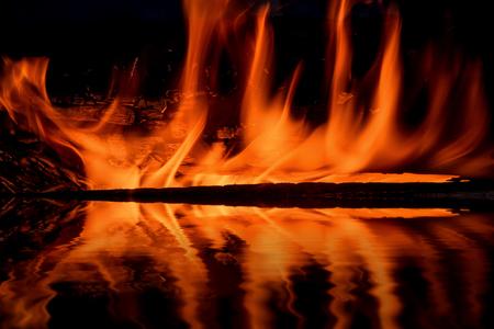 resplandor: pintorescas llamas de un incendio en un fondo negro con la reflexión en el agua Foto de archivo