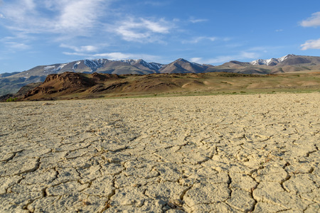 Scenic desert steppe landscape with mountains and the dry ground with cracks and sparse vegetation on a background of blue sky and clouds Stock Photo