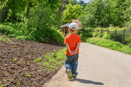 A little boy in an orange shirt and jeans walking along a path in a park Stock Photo