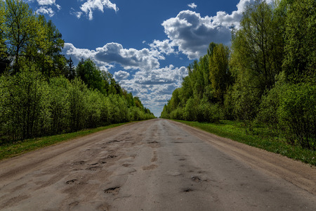 macadam: Scenic view of an asphalt road with holes and destroyed the road surface through the forest with tall trees on a background of blue sky and clouds Stock Photo