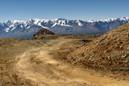 macadam: Scenic view with the gravel road on top of the mountain on the background of the mountains with snowy peaks and blue sky on a sunny day