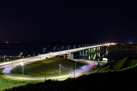 Scenic night top view with the river, reflections, road and bridge through river with lights and backlit