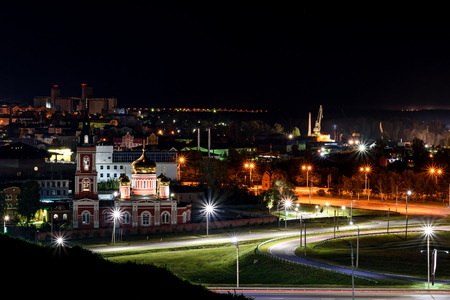 Scenic night view of the city with the church, houses, street lights and road Imagens