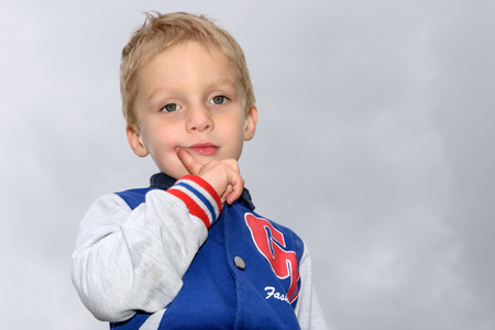 Portrait of a little blond boy on a light gray background cloudy sky