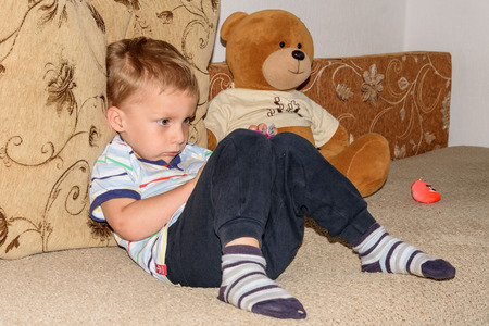 smeared baby: Portrait of fair-haired little boy playing with plasticine and bear home on the sofa Stock Photo