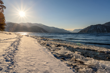 ice floe: Beautiful winter landscape with a lake, mountains, sun and footprints on the snow along the shore against a blue sky
