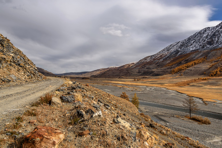 The picturesque autumn landscape with a rocky dirt road, winding river, mountains covered with snow and golden trees on a background of the sky and clouds Imagens