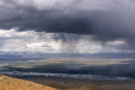 Scenic aerial view of the mountains covered with snow, hills and steppe against the background of a cloudy sky with storm clouds and rain Stock Photo