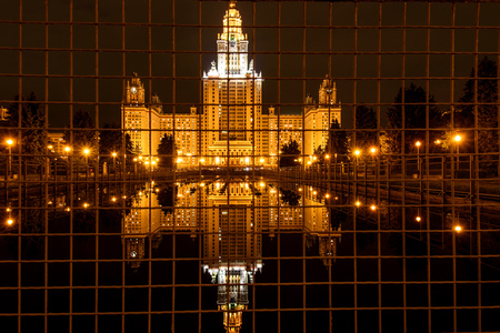 metal grid: A beautiful night view of Moscow with the main building of Moscow State University, lights and reflections in the water through the metal fence of the fountain