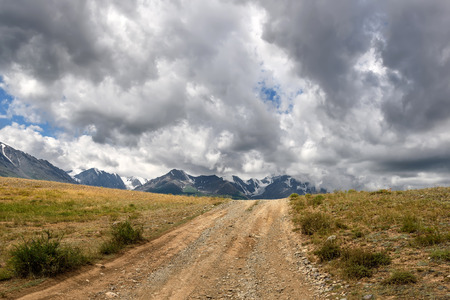 A picturesque view with a dirt road through the steppe to the mountains covered with snow against the background of a cloudy sky Imagens
