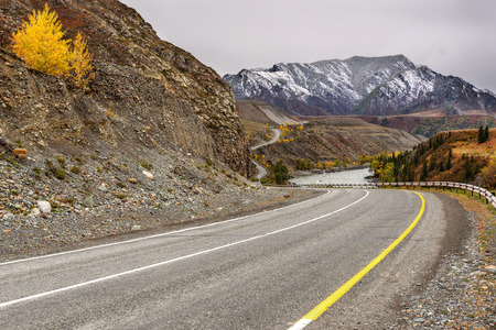 A colorful autumn landscape with a winding asphalt road along the river, mountains covered with first snow and a river on the background of the cloudy sky
