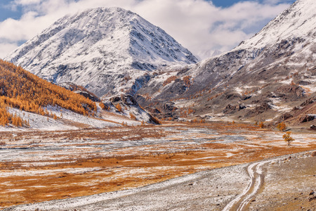 A colorful autumn view with a dirt road, the first snow, a winding river, mountains and golden trees on the slopes