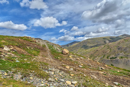Rocky dirt steep road up among the stones high in the mountains on the background of blue sky and clouds Stock Photo