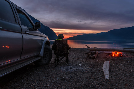 The tourist sits on the shore of the lake near a car and a fire and watches a beautiful sunset over the lake and mountains
