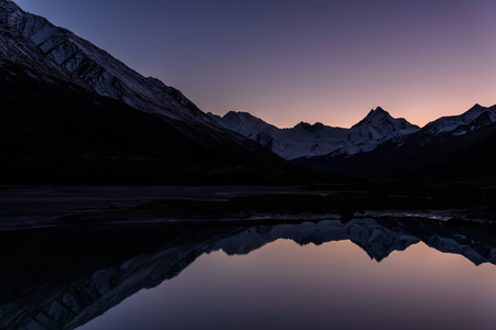 Amazing colorful sunset with a glacier and snowy mountains reflected in the smooth water of the lake in autumn Stock fotó