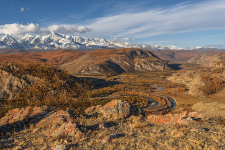 Amazing autumn landscape with a winding river, forest, golden trees, asphalt road and mountains covered with snow against a blue sky and clouds