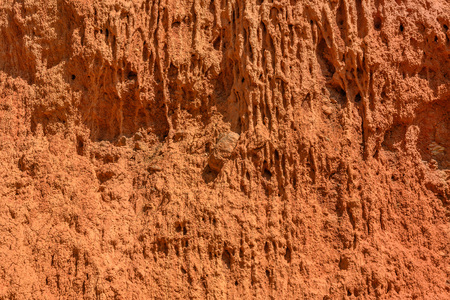 Abstract natural background from texture of the mountain slope with red soil, clay and stones