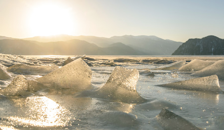 Beautiful view of frozen Lake Teletskoye with ice, floes and the sun over the mountains on a sunny morning
