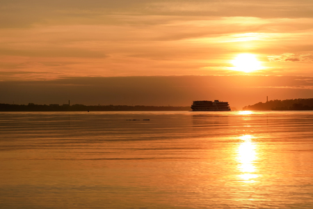 Amazing orange sunset on the Volga River with the sun, a steamer on the water and the contours of the city on the horizon 版權商用圖片