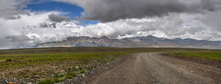 Amazing panorama with a gravel road through the steppe and colored mountains against a cloudy sky with beautiful clouds Archivio Fotografico