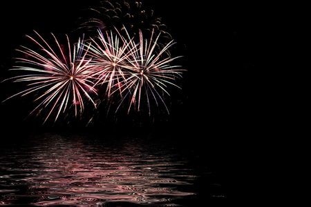 Abstract festive background with multicolored fireworks, salute on a black background and reflections in water