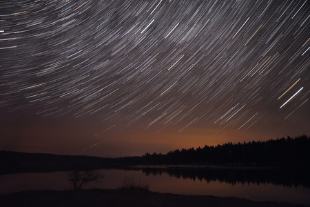 Amazing view of the night sky with stars in the form of tracks over the lake, forest and reflections in the water