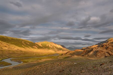Amazing top view of the mountains and the valley with a winding river in the first rays of sunlight against the backdrop of beautiful clouds at sunrise. Altai, Russia Banco de Imagens