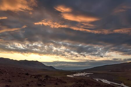 Amazing golden sunrise with mountains and a valley with a winding river in the first rays of sunlight on the background of the beautiful illuminated clouds on the sky. Altai, Russia