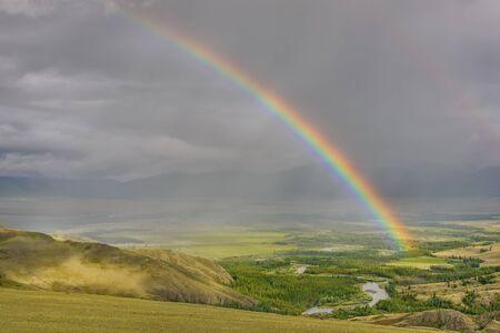 Increíble arco iris de colores brillantes sobre las montañas, un valle con un río sinuoso y un bosque contra un cielo tormentoso con nubes y lluvia. Altai, Rusia.
