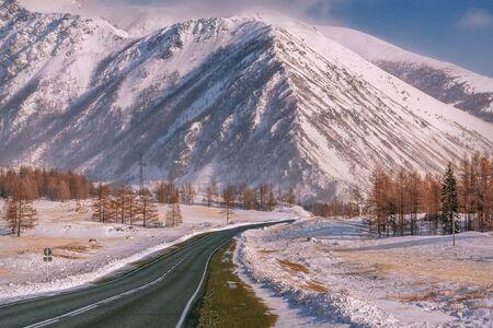 Malowniczy zimowy krajobraz z asfaltową drogą w górach pokrytych śniegiem i drzewami na poboczu drogi na tle błękitnego nieba i chmur