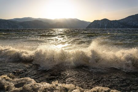 Amazing winter view of the lake, mountains, the sun, big waves, splashes and ice on the stones at sunrise. Teletskoye Lake, Altai, Russia